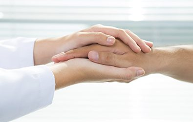 Two people holding hands for comfort